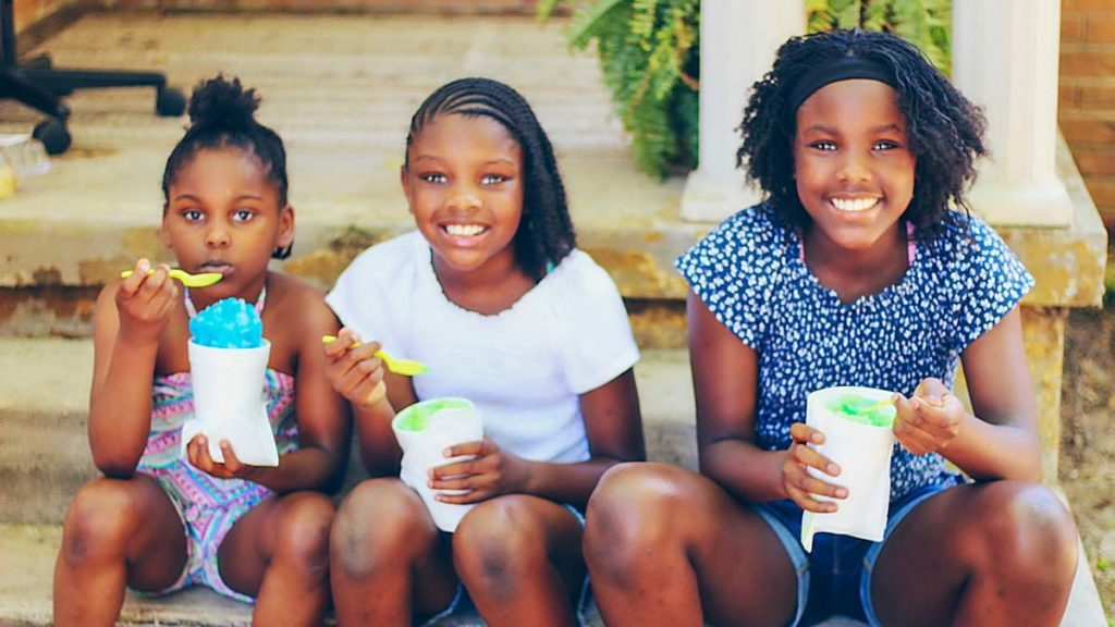 Three young black girls celebrate with ice cream at Dermott, Arkansas' Entrepreneurship Extravaganza.