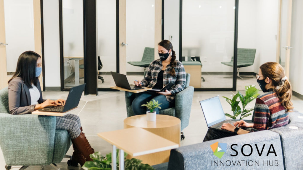 Three women in masks are seen sitting inside the newly opened SOVA Innovation Hub space.