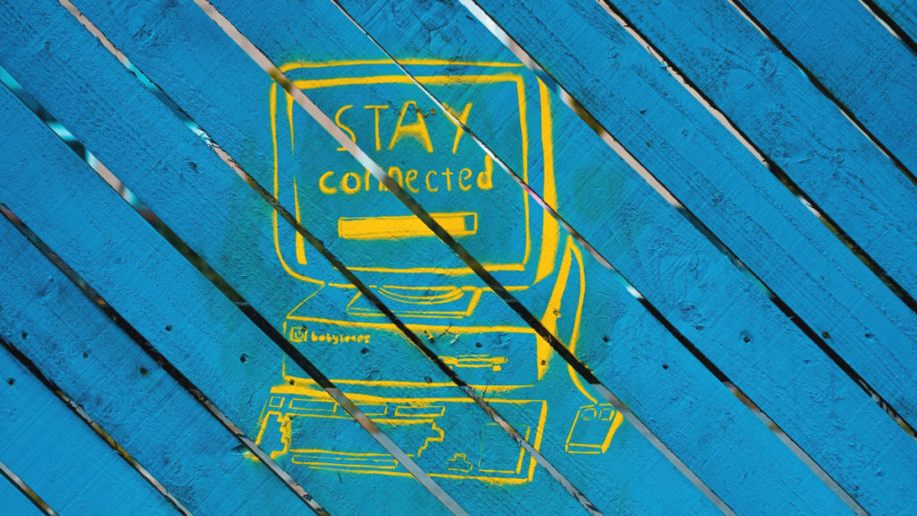"An illustration of a computer with the words ""stay connected"" is painted in yellow on a turquoise blue wooden background."